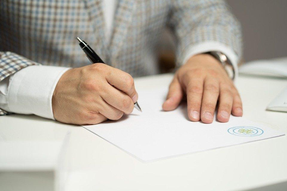 Hand-with-pen-signing-procurement-contract-relating-to-rebate-management